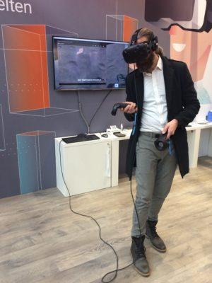 Learntec-Besucher mit VR-Brille in Aktion auf dem IMC-Messestand - Foto: IMC