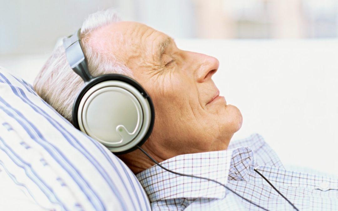 Seitenprofil eines älteren Mannes, der Musik mit Kopfhörern hört