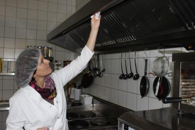 Lebensmittelkontrolleurin prüft Reinigungszustand einer Abluftanlage © BVLK